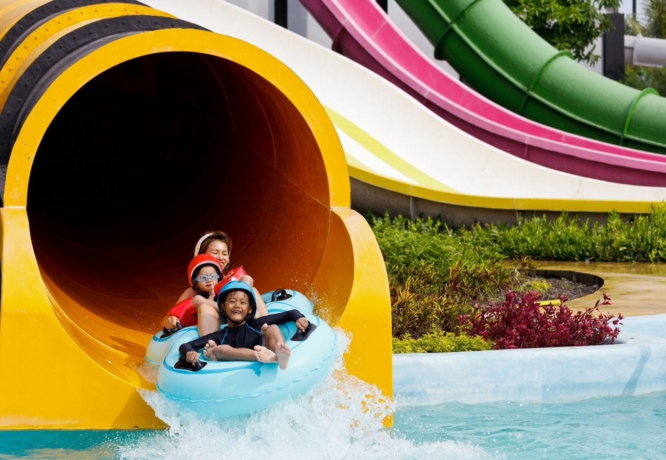 A mother and two kids sliding down a a giangt tube at a water park.