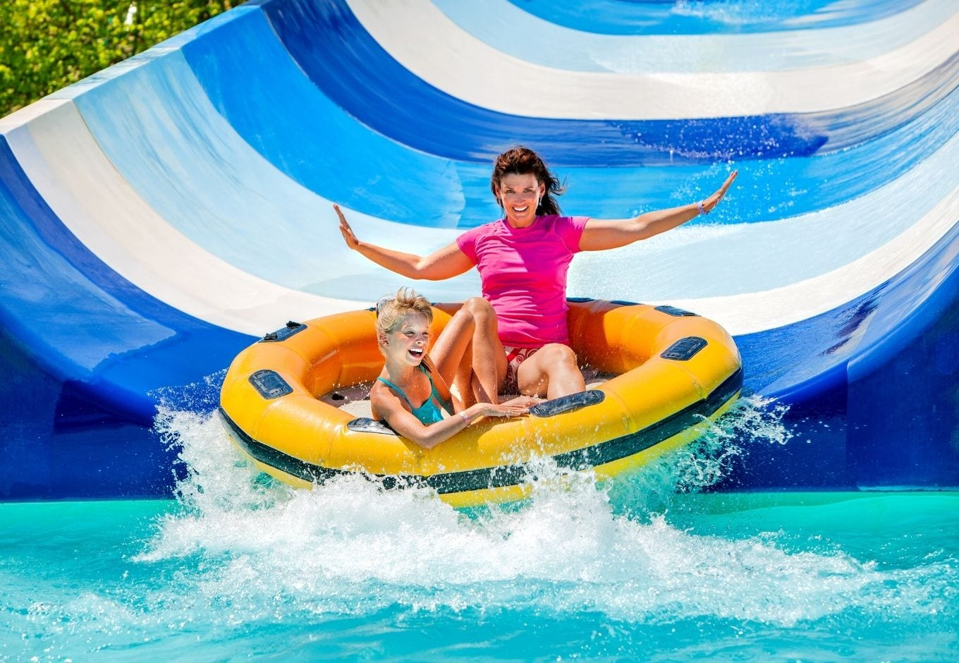 Mom and daughter having fun o a waterslide.