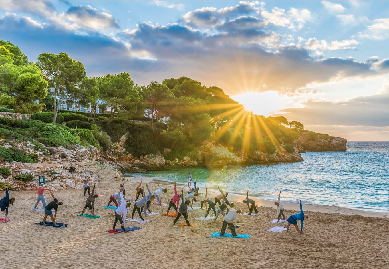 People practicing yoga at sunset time in Palma Mallorca Island, Spain