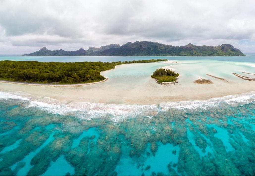 Aerial view of Raivavae island with sandy beaches, coral reef and green islets motu in azure turquoise blue lagoon