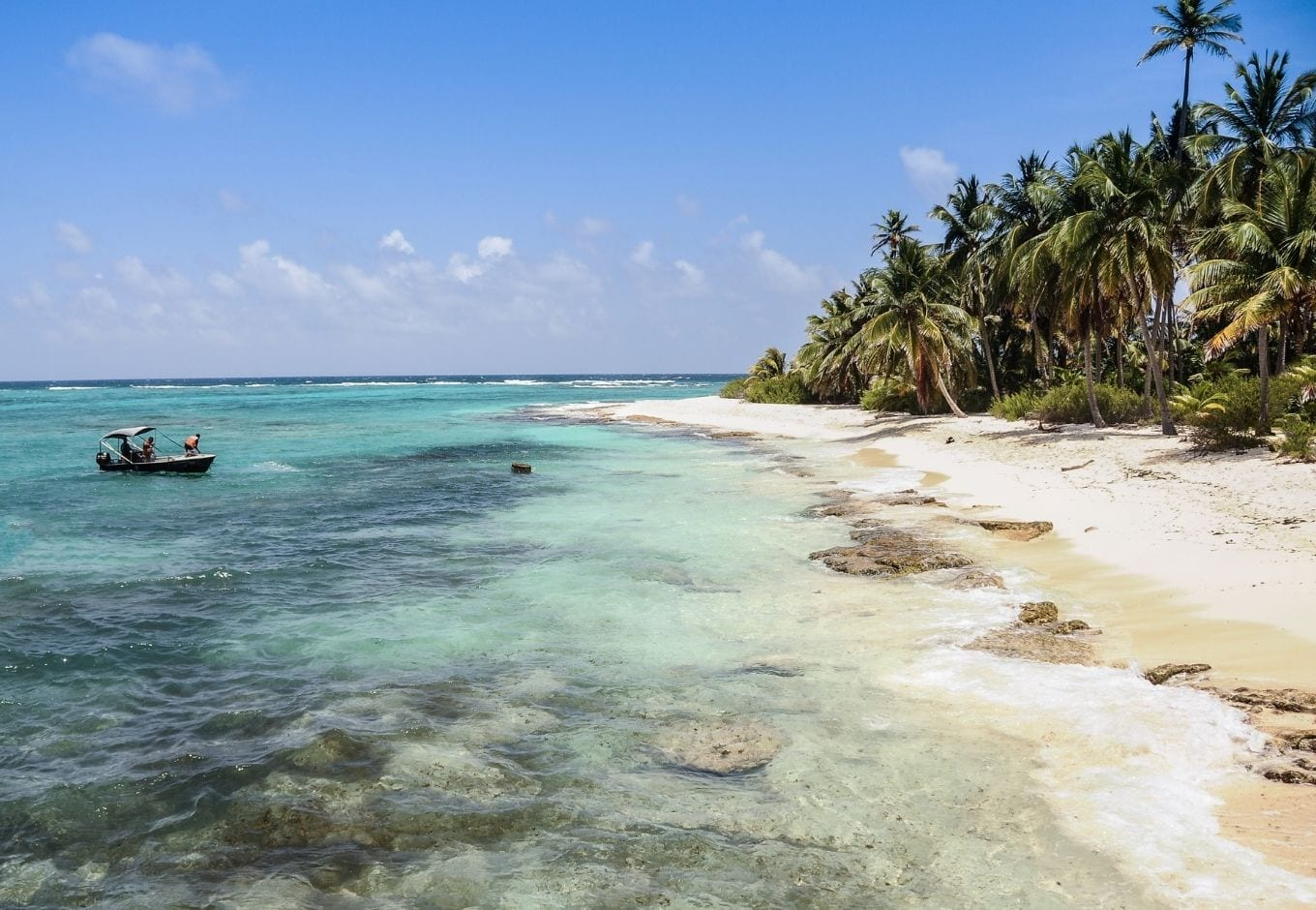 White sandy beach with palm trees and transparent blue-green water at San Andrés, in Colombia, South America.