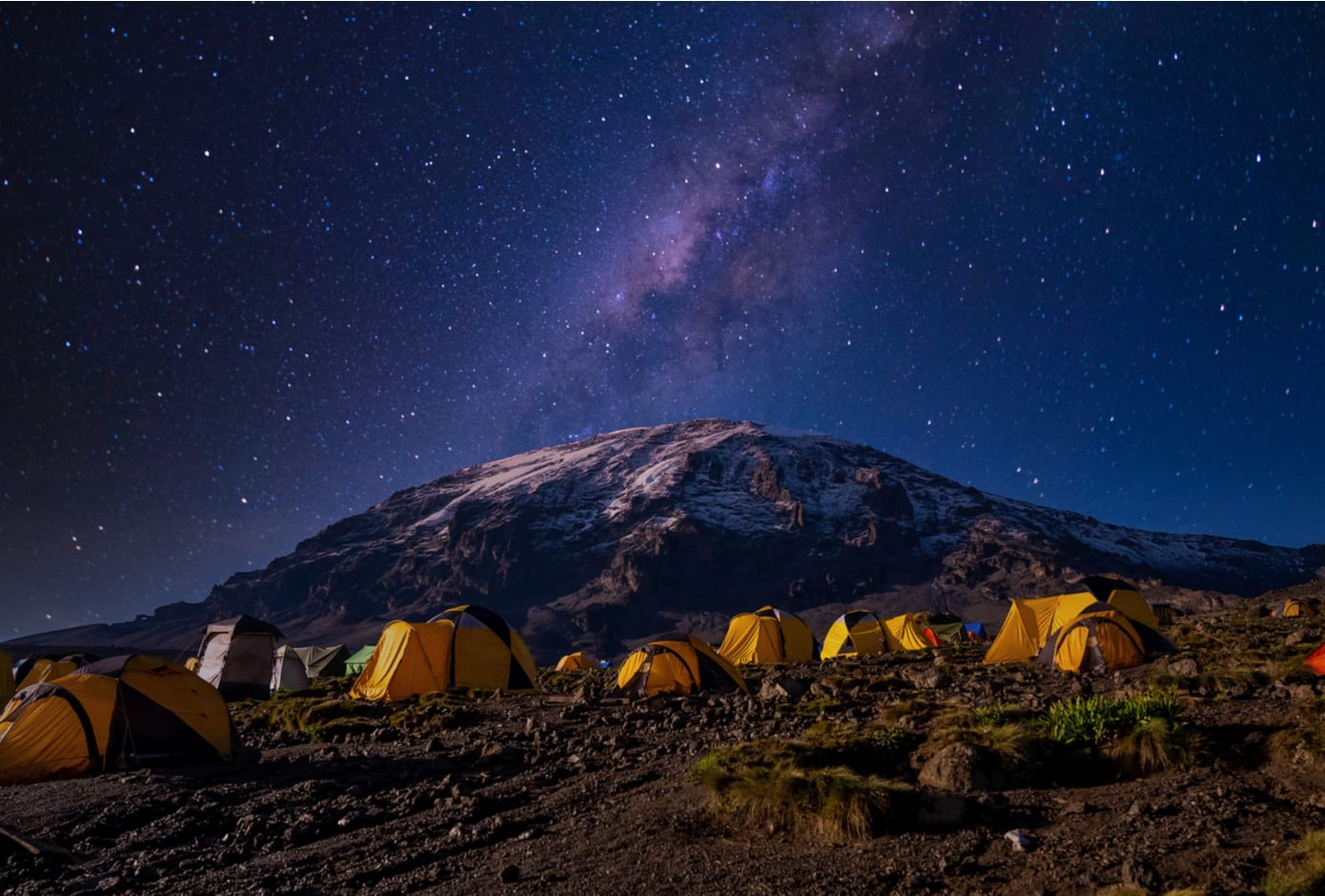 Night view of the milky way over mount Kilimanjaro, Tanzania with many tents at the base camp.