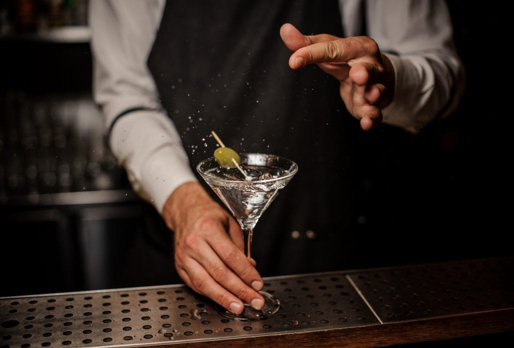 Bartender making a martini cocktail with a green olive and salt