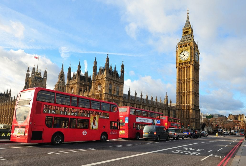 Three double-deck red buses in front of the Big Ben and the Westminster Palace in London.
