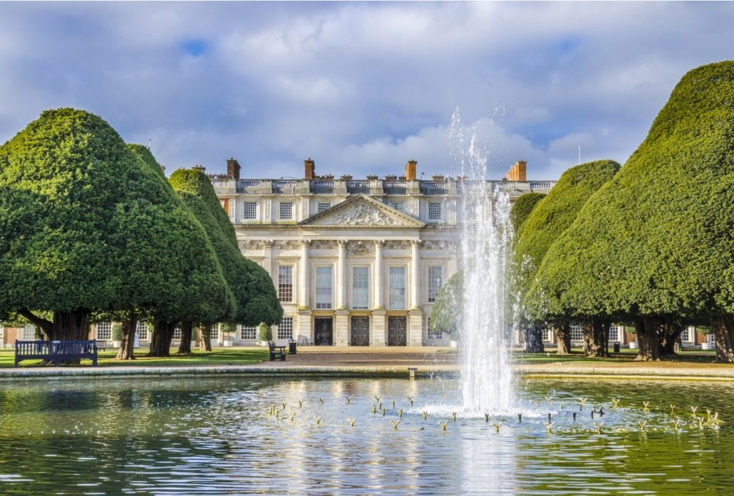 A water fountain and ornate trees in front ot the marvelous Hampton Court Palace, in London.