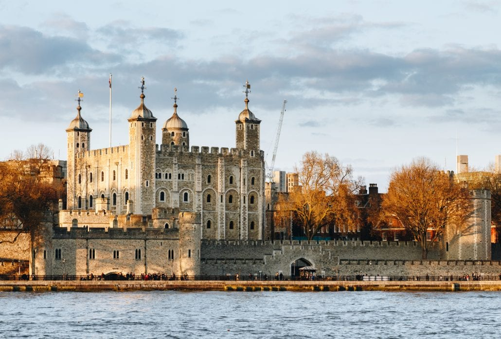 Tower of London at sunset, surrounded by autumn trees.