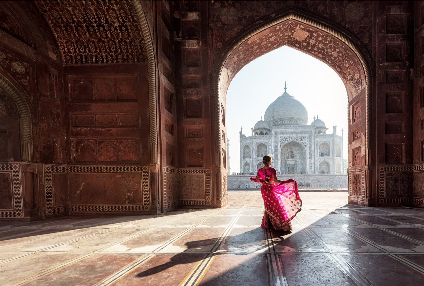 Woman with flowy red dress facing the Taj Mahal, in India.