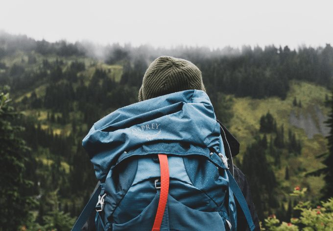A young backpacker man looking at a forest on a cloudy day.