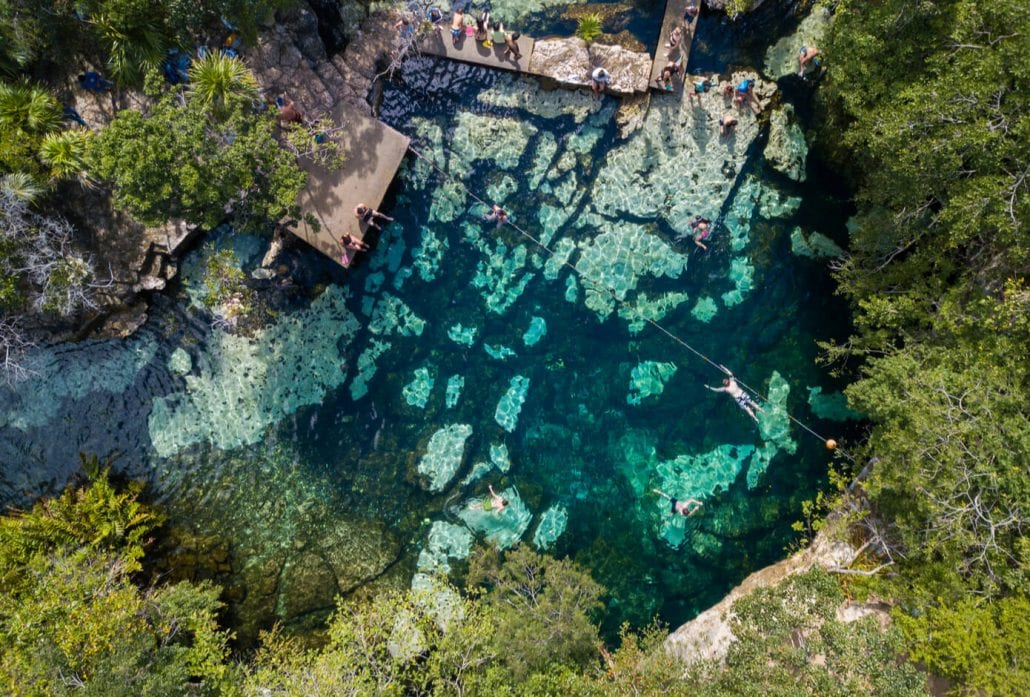 Tree people swimming in the turquoise-waters of the Samula Dzitnup Cenote, Mexico.