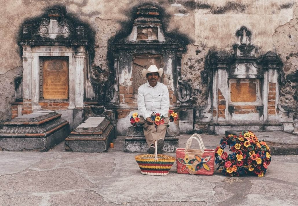 Portrait of a Mexican man peacefully sitted on a grave, in Mexico, and holding colorful flowers.