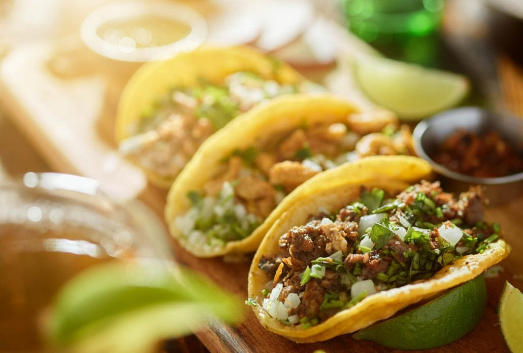 Three Mexican tacos on top of a wooden board.