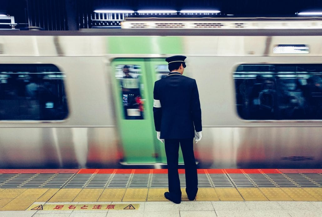 A metro employee standing in front of a passing train inside the Shibuya Station, in Tokyo, Japan.