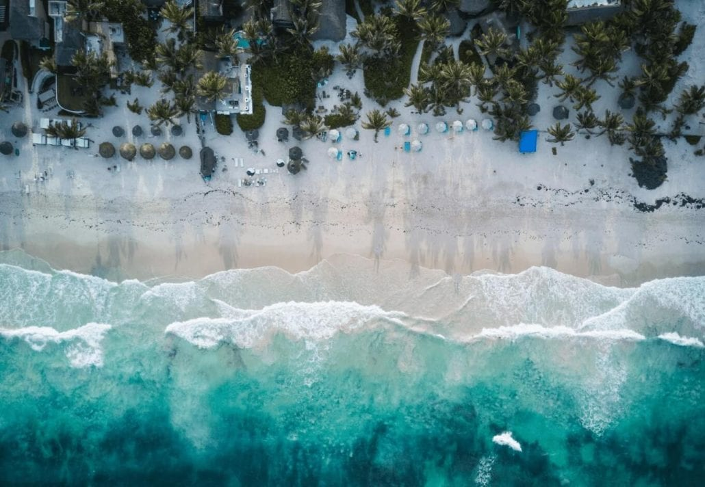 Aerial view of Tulum beach with turquoise-blue waters and alabaster white sand in Mexico.