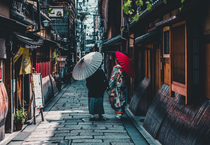 Two Japanese women dressed in traditional kimonos strolling in the streets of Kyoto, Japan.