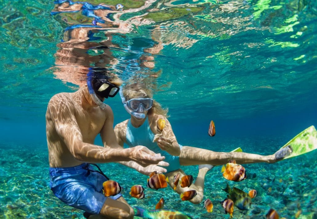 Young couple in snorkeling mask hold hand, dive underwater with fishes in coral reef sea pool.