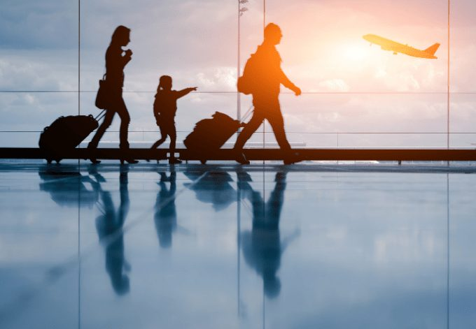 Silhouette of young family walking at the airport and and an airplane on the background.