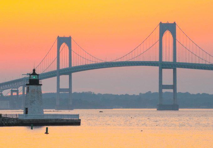 Newport Harbor Lighthouse and the Newport Bridge at sunset, located in the Narragansett Bay.