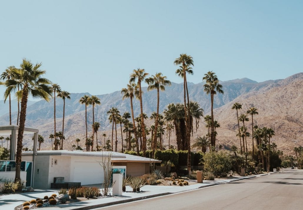 The desert city of Palm Springs framed by mountains and palm trees in California, US.