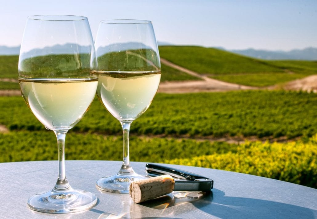 Two white wine glasses at a table overlooking the Sonoma County, in California.