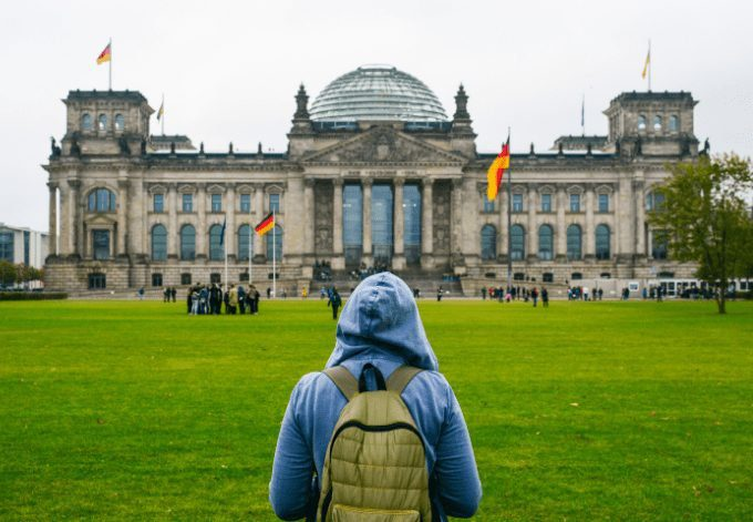 Young woman with backpack looking at the Bundestag building in Berlin. Erasmus student, studying abroad and tourist concept.
