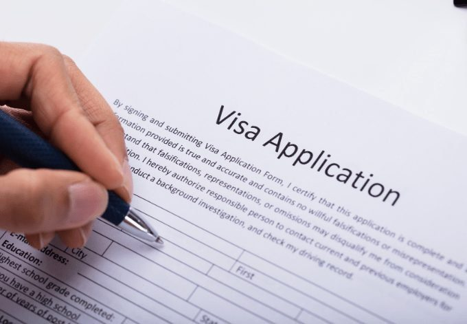 Close-up of a Person's Hand Filling Visa Application Form