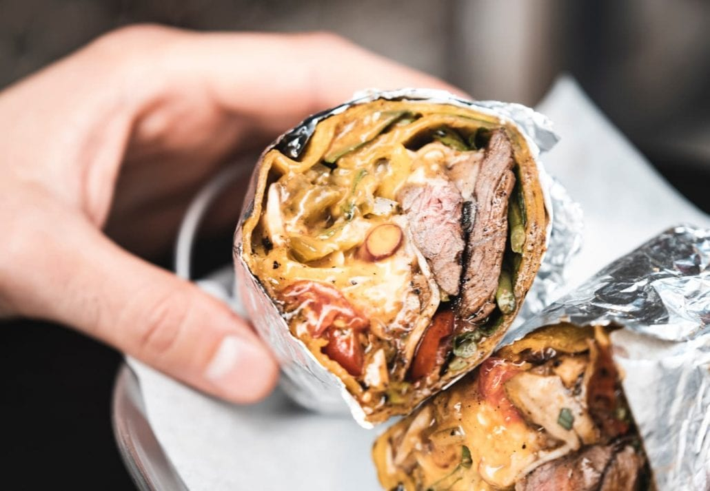 Person holding a giant Mexican burrito cut in half.