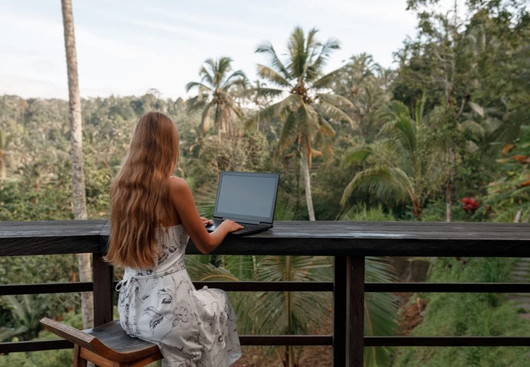 Remote work in tropic country. Woman working with laptop wjile sit in cafe with jungle view, coconut palms around