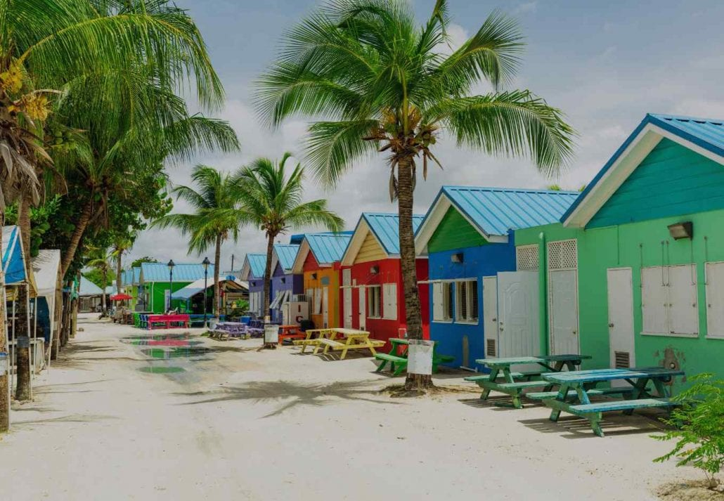 Colorful houses lined up by a white sand beach in Barbados.
