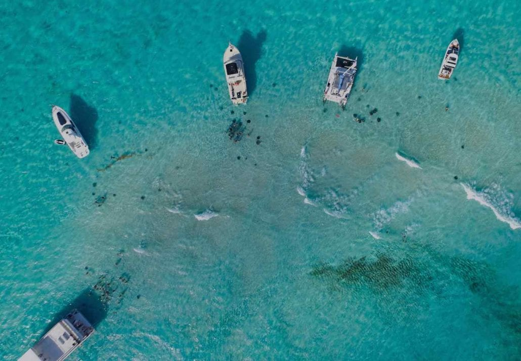 Boats on the transparent blue ocean in the Cayman Islands.