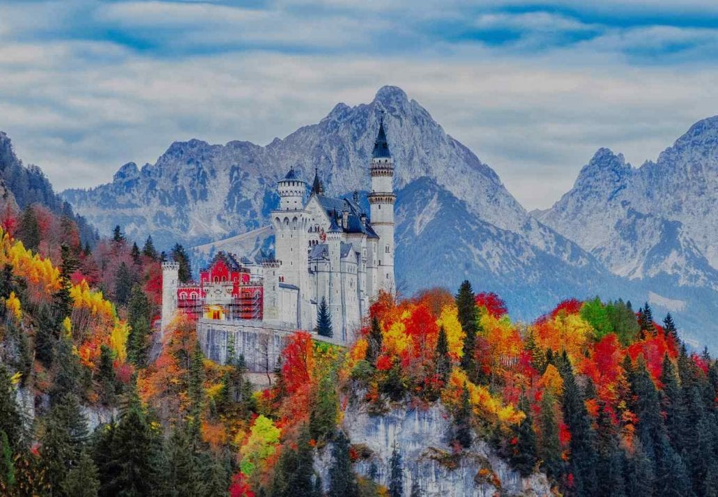 The neuschwanstein castle surrounded by orange, yellow and red fall foliage, in Germany.