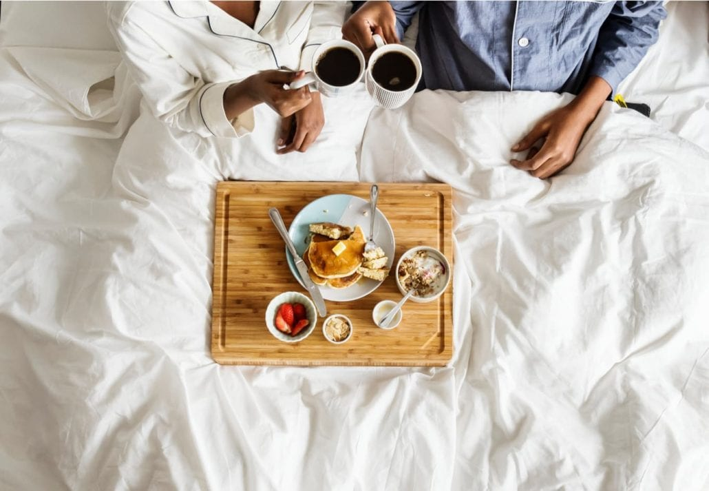 Couple eating breakfast in bed.