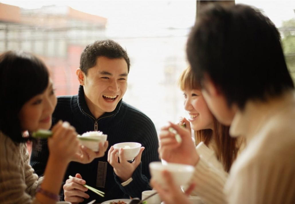 Group of Chinese friends eating rice and laughing.