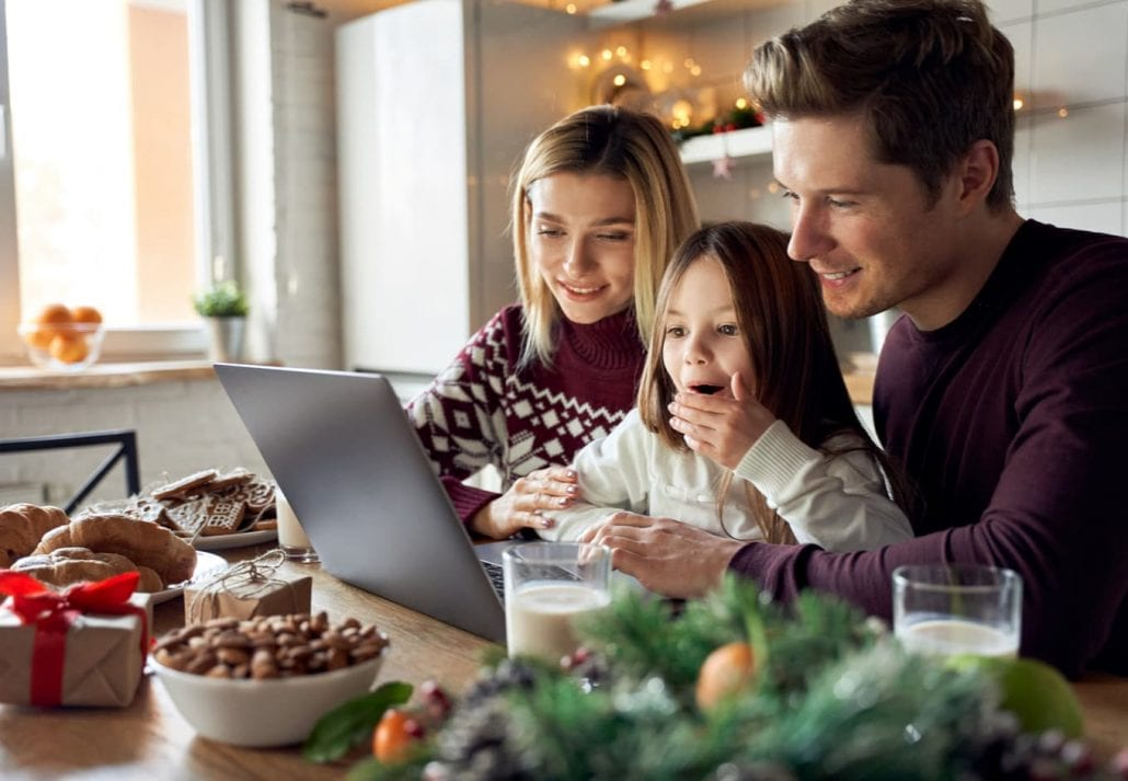 Happy young parents with cute excited small kid daughter using laptop computer at home sitting at Christmas table