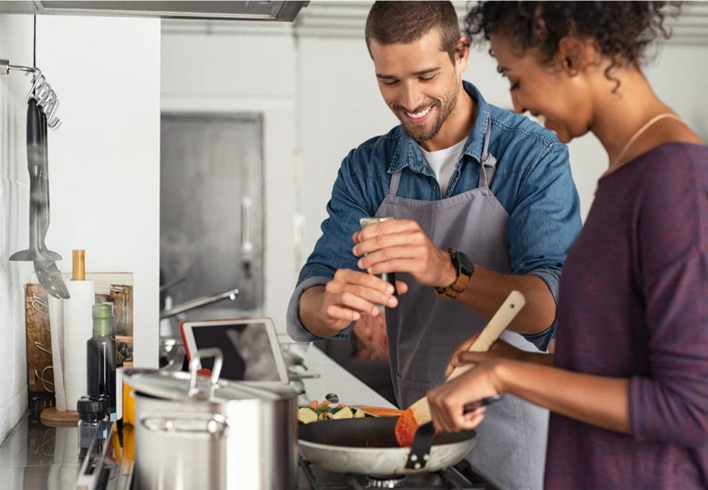Young man cooking with girlfriend and adding spice to the sauce.