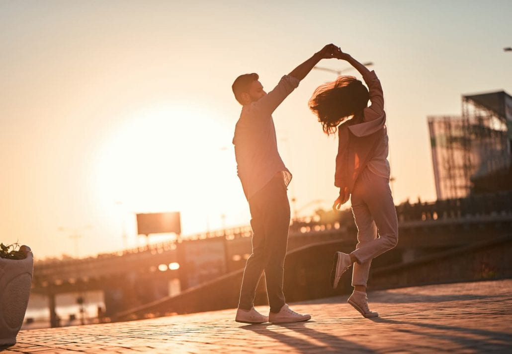 Young couple dancing outdoor at sunset.