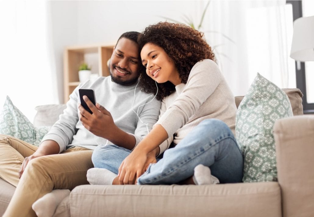 Happy couple with smartphone and earphones at home
