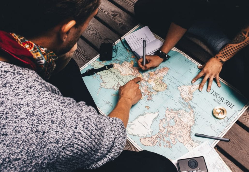 Young couple planning a trip while reading a map.