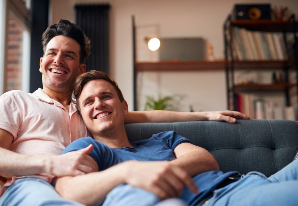 Male Couple Lying On Sofa At Home Watching TV And Relaxing Together