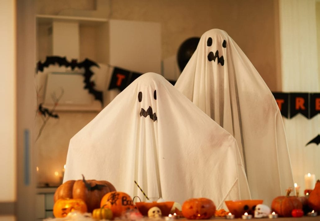 Portrait of children dressed in ghost costumes they standing in the room and celebrating Halloween