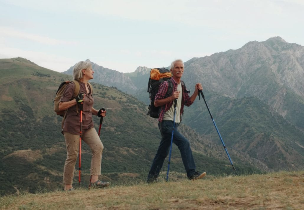 Active senior couple hiking in mountains with backpacks enjoying their adventure.