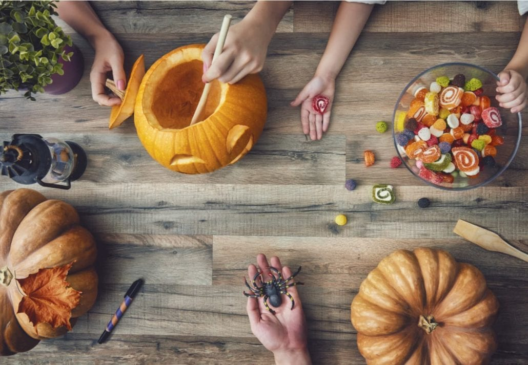 A mother, father and their daughter carving pumpkin on the table at home. Family getting ready for Halloween.