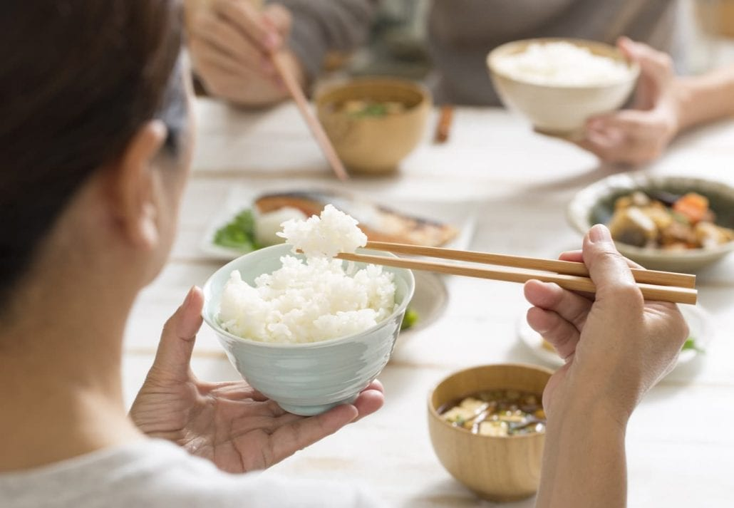 Japanese woman eating rice during a typical dinner meal.