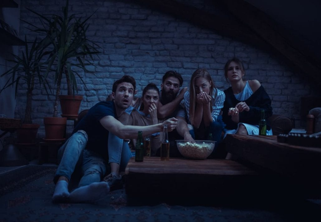 Group of friend watching scary movie at home
