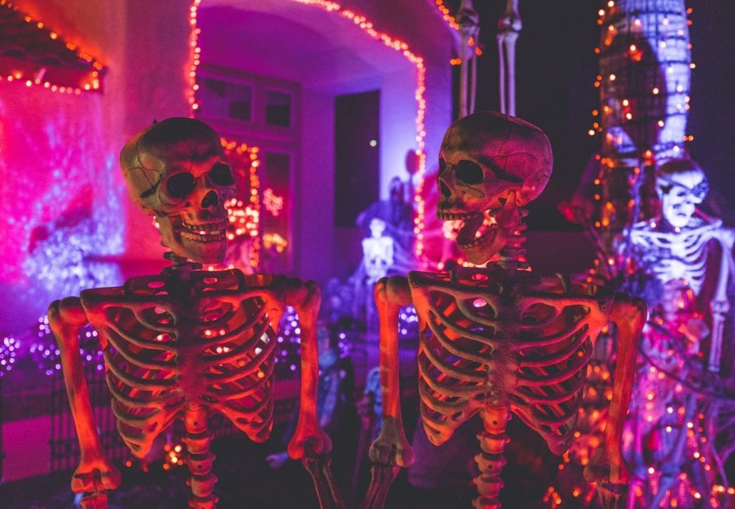 Halloween decoration with skeletons and lights at a house at night.