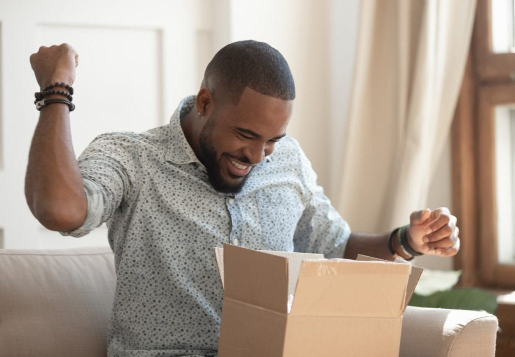 Excited men opening a package.