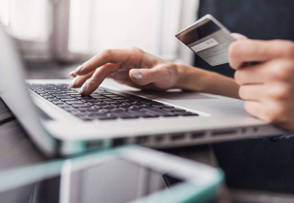 Woman holding a credit card and shopping online on her laptop.