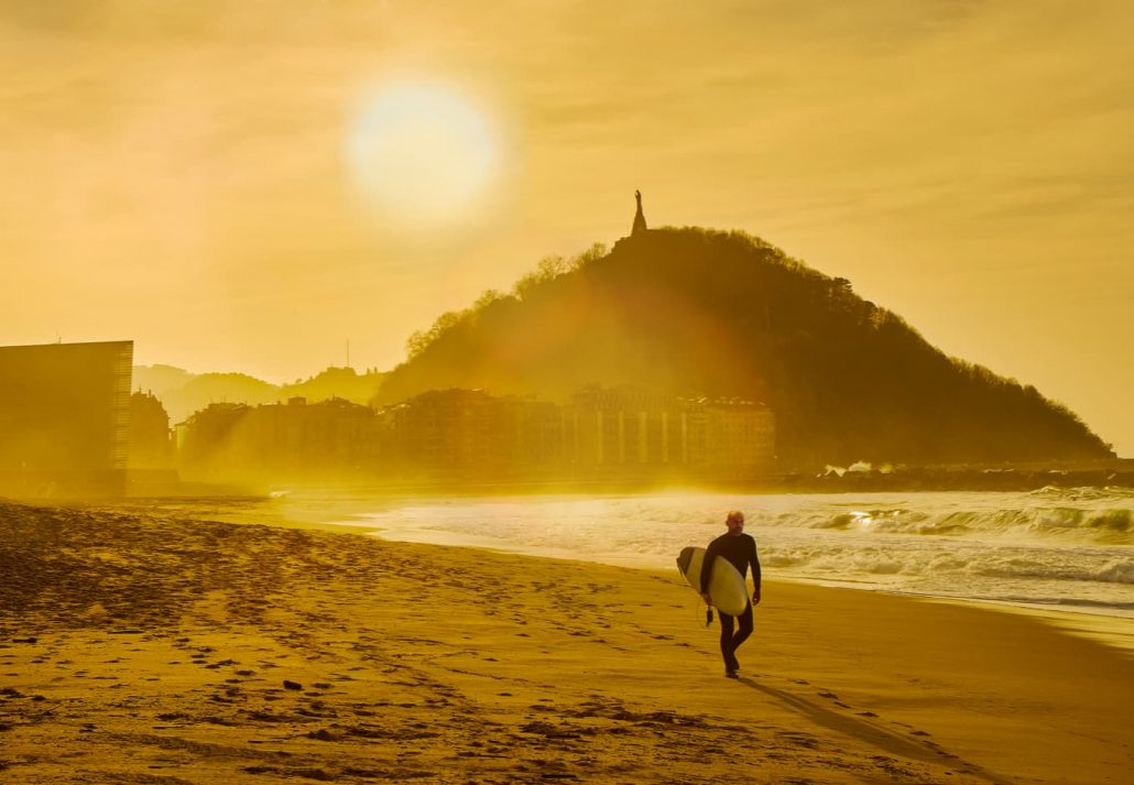 A surfer walking on the Zurriola Beach at sunset with the Monte Urgull in the background. San Sebastian, Basque Country, Guipuzcoa.