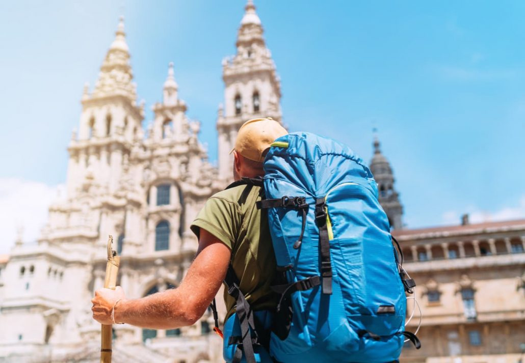 Backpacker man pilgrim looking at Santiago de Compostela Cathedral standing on the Obradeiro square (plaza)
