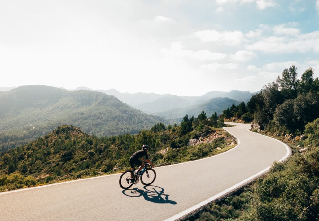 Cycling through a road surrounded by mountains.