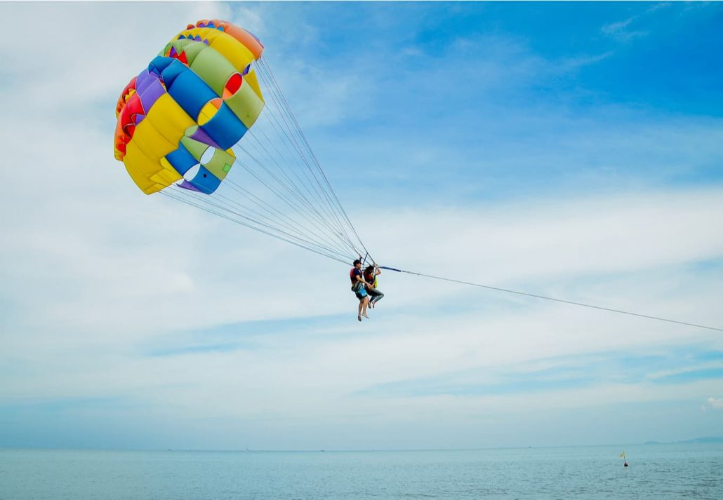 Tourists parasailing in the blue sky over the ocean.
